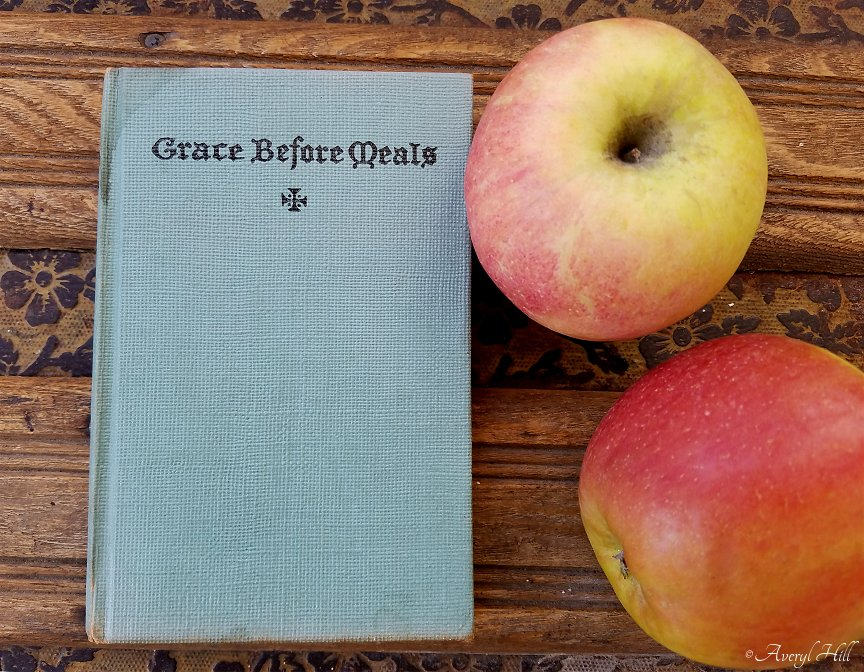 vintage book grace before meals on antique steamer trunks with apples