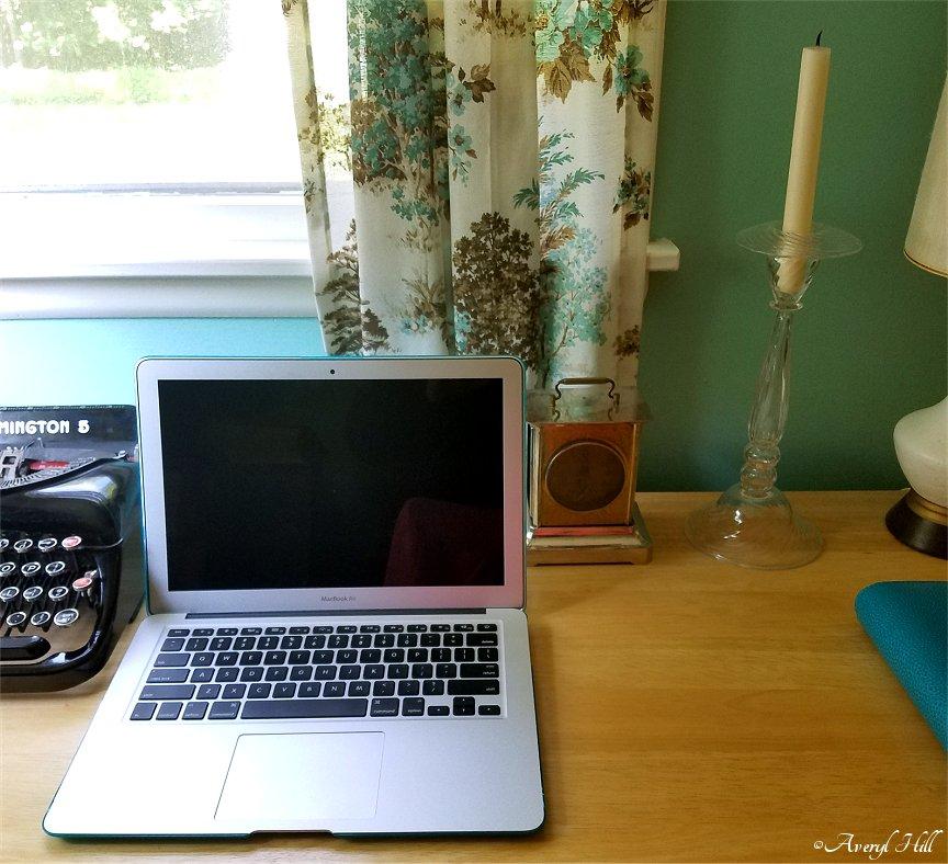Laptop on desk next to typewriter