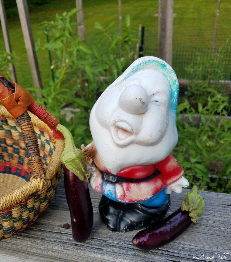 Dwarf statue holding garden eggplant