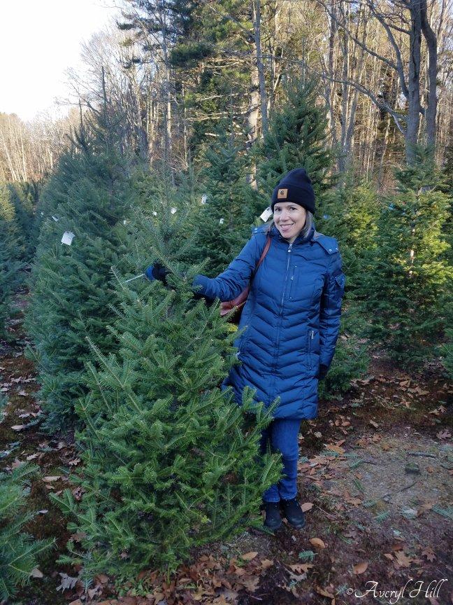 Averyl holding up freshly cut Christmas tree